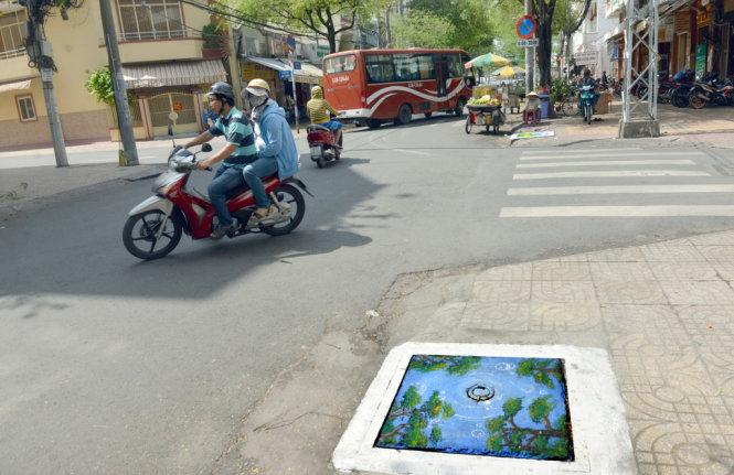 Đường phố đẹp hơn kể từ khi xuất hiện những bức tranh trên nắp cống - Ảnh: DUYÊN PHAN