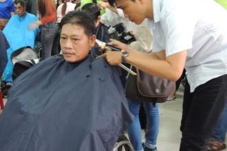 Anh Hàn Văn Thắng được tình nguyện viên cắt tóc. Ảnh: THU HƯỜNG