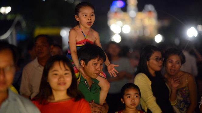 Một em nhỏ thích thú xem biểu diễn nghệ thuật đường phố - Ảnh: Quang Định