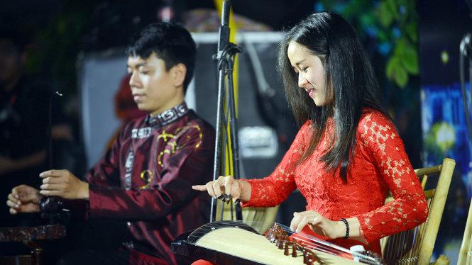 Một nghệ sĩ biểu diễn đàn tranh trong chương trình Nghệ thuật đường phố tại phố đi bộ Nguyễn Huệ, Q.1, TP.HCM tối 13-5 - Ảnh: Quang Định