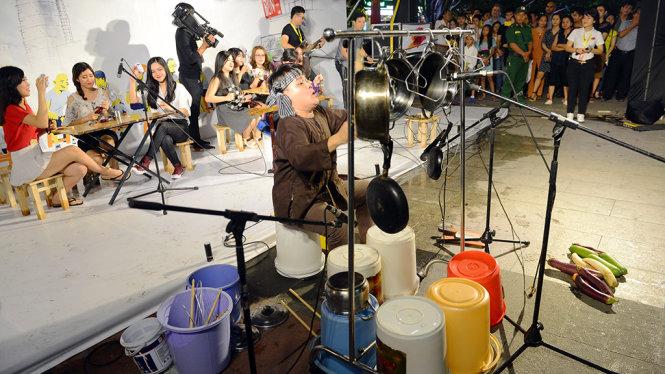 Nghệ sĩ biểu diễn với thùng, nồi, xoang,... trong chương trình Nghệ thuật đường phố tại phố đi bộ Nguyễn Huệ, Q.1, TP.HCM tối 13-5 - Ảnh: Quang Định