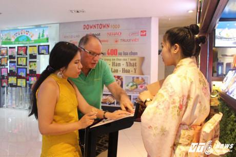 Nhân viên cửa hàng Nhật Bản đang giới thiệu món ăn với du khách.
