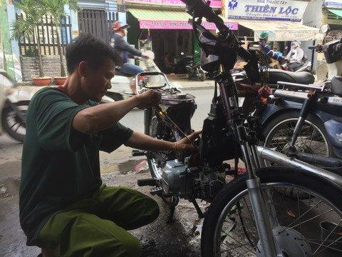Sửa xe gắn máy cho khách, công việc mưu sinh hàng ngày của anh Thái.