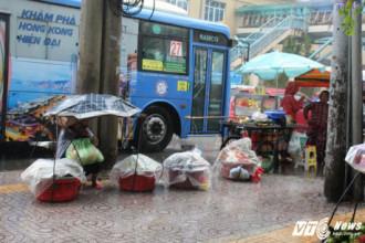 Bất chấp trời mưa, nhiều người bán hàng rong vẫn co ro bán hàng trên vỉa hè.
