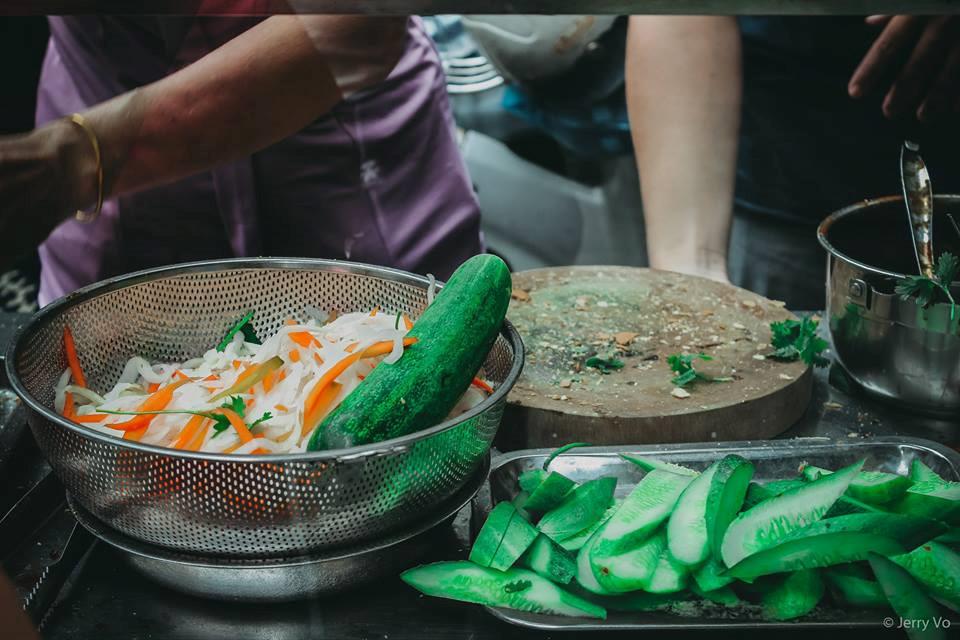 Một ổ bánh mì có các loại dưa chua, dưa leo, hành ngò, với 5 viên thịt nướng cùng nước sốt đậm đà.