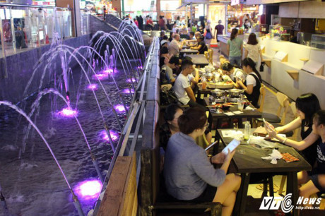 Bể phun nước ngay cạnh dãy bàn ăn.