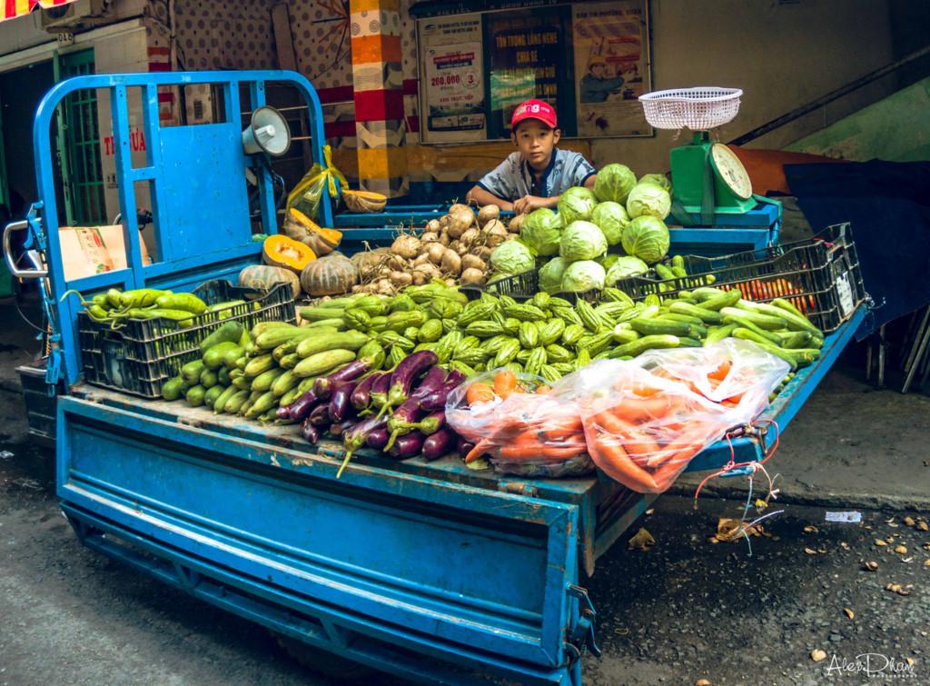 Cậu bé ngồi lặng chờ đợi khách đến mua rau củ. Những góc thiếu sáng trong bức ảnh vẫn rõ ràng, không bị mất chi tiết.