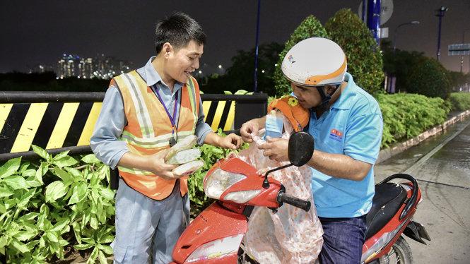 Anh Nguyễn Ngọc Minh, nhân viên cứu hộ đường hầm sông Sài Gòn, phát áo mưa miễn phí cho người đi đường - Ảnh: HỮU THUẬN