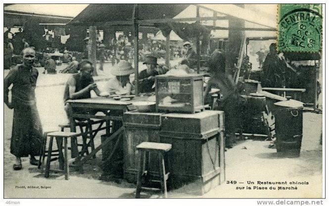 Một quán hủ tíu trên đường Charner, trước chợ Bến Thành cũnăm 1908(dòng chữ trên bưu ảnh ghi: Một quán ăn Trung Hoa trướcchợ) với thưc khách ngồi chồm hổm trên ghế- Ảnh tư liệu