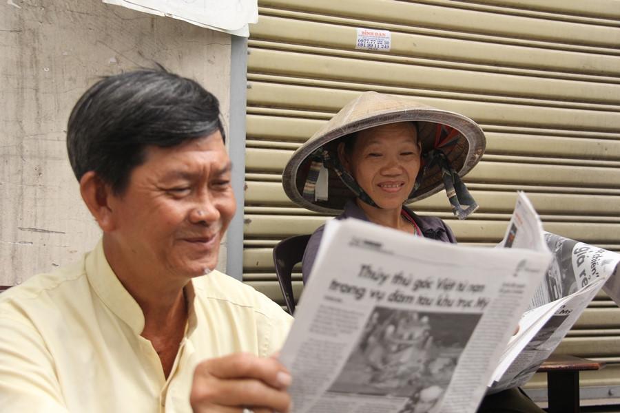Hai vợ chồng vừa bán báo, vừa bàn luận tin tức thời sự trong ngày.