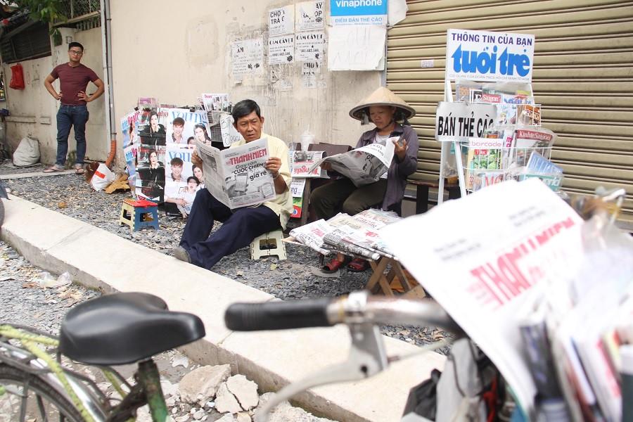 Mỗi sáng ông Sơn ghé thăm sạp báo của vợ một lần, sau đó đi bán báo quanh thành phố rồi mới trở về ăn cơm trưa cùng vợ. ẢNH LÊ NAM