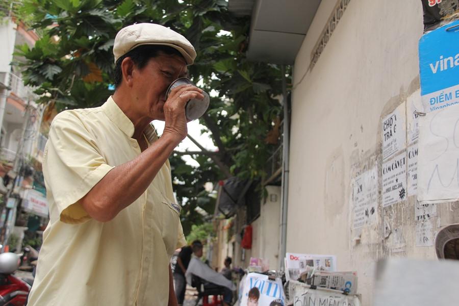 Sau khi nghỉ chân uống ngụm nước mát lành, ông Sơn lại tiếp tục rong ruổi trên đường phố để rao báo. ẢNH LÊ NAM