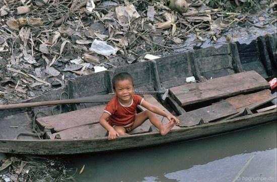 Một em bé trên chiếc thuyền nan.