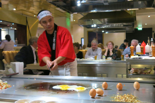 Một nhà hàng trong khu Mailbox ở trung tâm thành phố, khách ngồi quanh bàn coi đầu bếp nấu và có thể lên trải nghiệm việc nấu nướng để chụp hình nếu muốn.