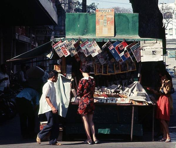 Đừng nghĩ phụ nữ Sài Gòn cách đây nửa thế kỷ chỉ biết ăn diện mua sắm, mà đọc báo cũng là một thú tao nhã của chị em. Trong ảnh là một cô gái đứng mua báo tại một kiôt góc đường Tự Do - Nguyễn Văn Thinh (nay là Đồng Khởi - Mạc Thị Bưởi).