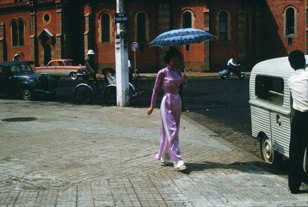 Một người phụ nữ Sài Gòn mặc áo dài phi bóng tím, tay cầm dù đang ung dung dạo phố tại Công Xã Paris trước 1975.