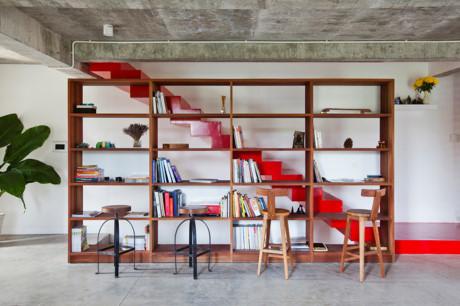 Một giá sách lớn đặt cạnh cầu thang là không gian đọc sách rất thú vị với những chiếc ghế ngồi phá cách.