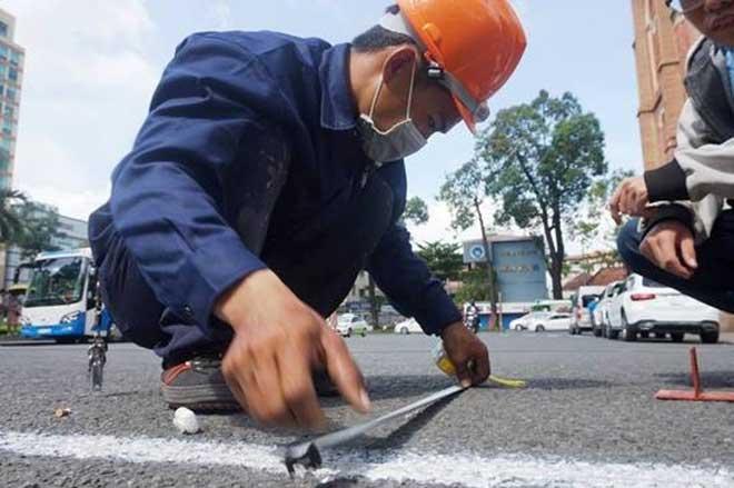 Các công nhân đo đạc để dựng rào chắn trùng tu nhà thờ Đức Bà