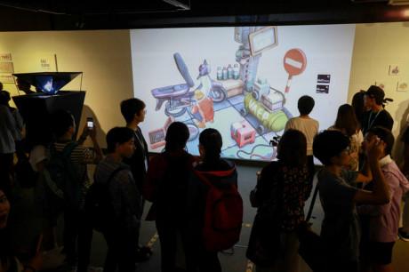 """""""Tại triển lãm chỉ có mô hình vá xe lề đường 3m2 là thật. Còn trong không gian chính, chúng tôi thể hiện qua nhiều phiên bản khác nhau như trình chiếu 3D, hologram, mô hình đồ chơi và góc trưng bày tranh vẽ"""", Thái Thanh, đại diện nhóm triển lãm, nói."""