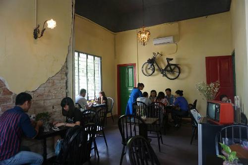 Quán đậm chất Sài Gòn xưa với những mảng tường bong tróc, cửa gỗ, tivi trắng đen và chiếc xe đạp treo trên tường.