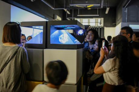 """Bạn trẻ xem không gian """"Sài Gòn 3 mét vuông"""" thông qua hologram, một kỹ thuật trình chiếu 3D hiện đại."""