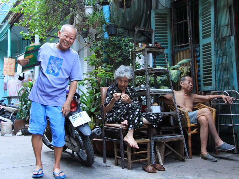 """Ông Hoa Trọng Tôn (68 tuổi, áo xanh) và cụ bà Diệp Liên (98 tuổi), người cao tuổi nhất trong hẻm chiều đến lại xách ghế ra hẻm ngồi nói chuyện với nhau. Ông Tôn cho biết: ngày trước ở đây toàn người Hoa, nay có thêm người Việt nhưng đa phần người dân trong hẻm vẫn nói chuyện với nhau bằng tiếng Hoa. """"Nay chiều chỉ có mấy người già ra ngồi chứ cách đây mấy chục năm chiều nào cả xóm cũng ra ngồi nói chuyện rôm rả, vui lắm!"""", ông Tôn chia sẻ."""