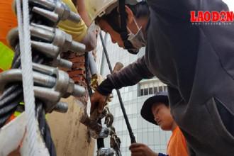 Công nhân đang tiến hành thay cáp cho cột cờ Thủ Ngữ 152 năm tuổi. Ảnh: Trường Sơn