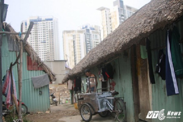 Mái nhà lá tạm bợ nép bên cạnh những tòa nhà cao ốc giữa Sài Gòn. (Ảnh: Dương Thương)
