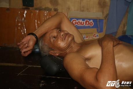Ông Nguyễn Văn Hoanh ngả lưng trên chiếc gối tự chế từ miếng mút lượm từ công trình. (Ảnh: Dương Thương)