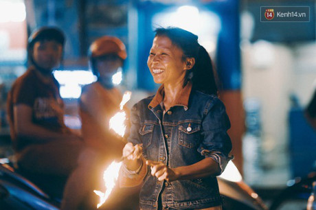 Người mẹ chơi đùa với lửa mỗi đêm ở Bùi Viện để kiếm tiền nuôi 2 con ăn học.
