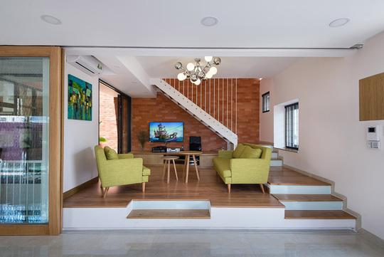 Phòng khách được thiết kế nâng cao nền, tách biệt với không gian bếp.