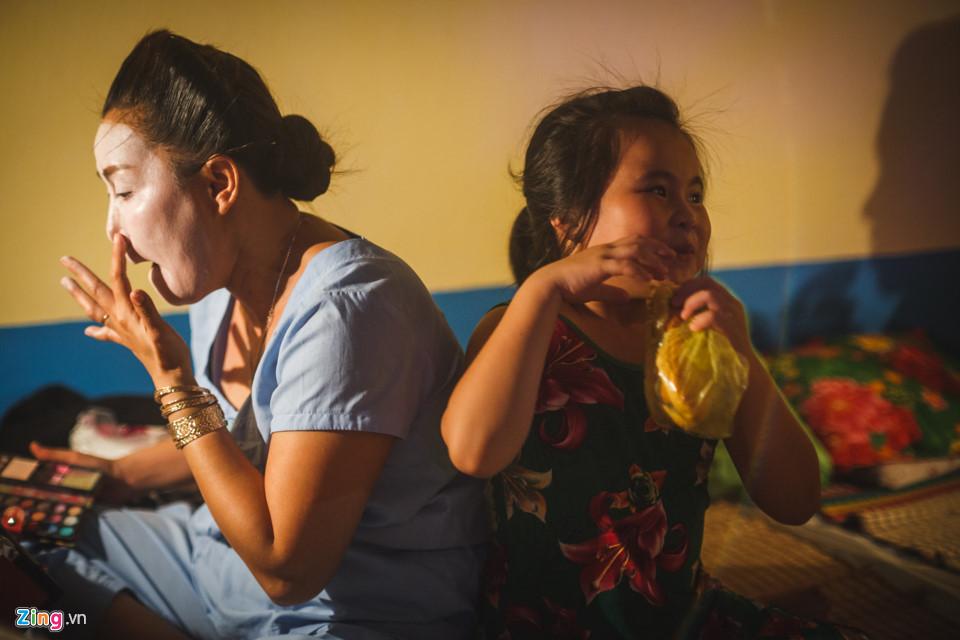 Gần đó, nghệ sĩ Băng Kiều (con gái của nghệ sĩ Hề Lạc) cũng đang vẽ mặt, trong khi cô con gái Lê Yến Nhi (8 tuổi) đang chơi đùa. Bé được đi theo mẹ lưu diễn trong thời gian nghỉ hè.