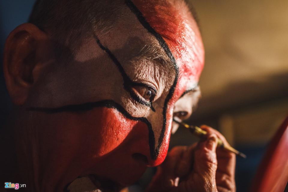 """Trong nghệ thuật hát bội, những màu sắc chính được trang điểm trên khuôn mặt thường để phân biệt tính tình, nhân sinh quan cũng như đạo đức của một nhân vật. Theo đó, sắc đỏ biểu thị cho người ngay thẳng, trung thành, đen tượng trưng cho người mạnh mẽ, hung tợn, trắng là người đa nghi, xảo trá,... Trong ảnh, nghệ sĩ Hề Lạc đang vẽ màu đỏ lên mặt, biểu thị cho trung thần. Năm nay đã 69 tuổi và theo nghề hát bội từ năm 14 tuổi, nghệ sĩ Hề Lạc tâm sự: """"Tui học hát từ ba tui, rồi tui dạy cho con gái tui, cả gia đình đều theo nghề hát. Bây giờ khó khăn quá, người ta ít đi coi hát lại, tui buồn lắm chứ, nhưng mà hát là đam mê của tui rồi, không bỏ được, tới chừng nào còn sức là còn hát"""". Trong hộp cá nhân của ông, lúc nào cũng có lọ thuốc vitamin, ông uống trước khi lên sân khấu để có sức diễn."""