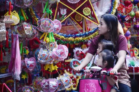 Hai bé gái tò mò, thích thú khi được người thân đưa đi mua lồng đèn.
