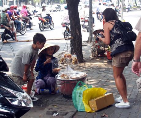 Du khách nước ngoài chụp ảnh người bán hàng trên đôi gánh trên phố Sài Gòn.