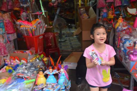 Một em bé tỏ ra thích thú được bố đưa đi lựa lồng đèn, đồ chơi trên phố lồng đèn Lương Nhữ Học.