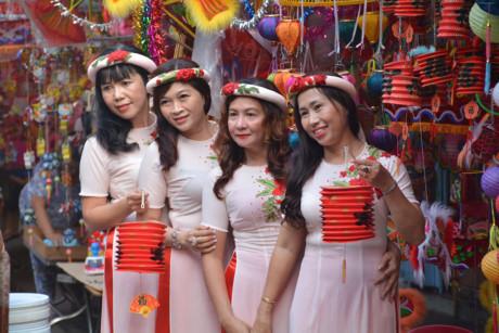 Một nhóm phụ nữ diện áo dài chụp hình kỷ niệm bên những chiếc lồng đèn đủ màu sắc.