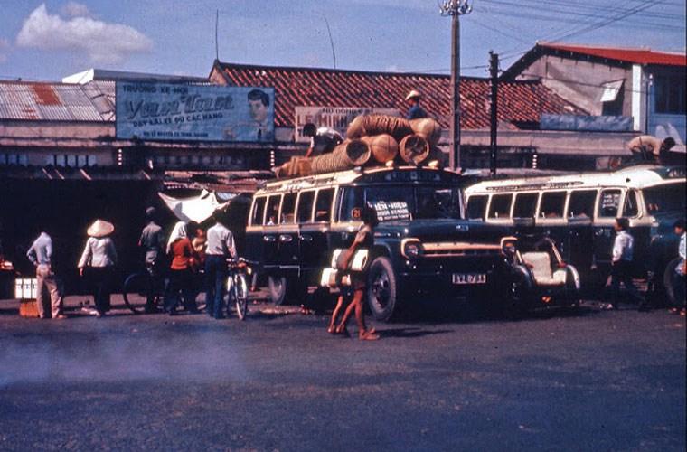 Hai xe khách đang xếp hàng và đón khách trước cửa tiệm bán hàng. Ảnh VT