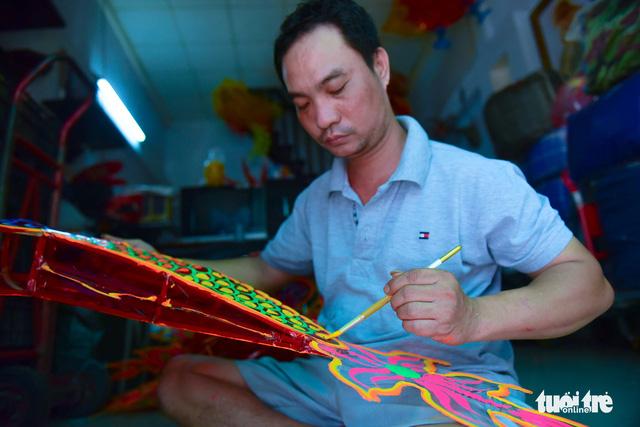 Anh Nguyễn Trọng Bình (40 tuổi) đã có tới gần ba chục năm trong nghề làm lồng đèn - Ảnh: HỮU THUẬN