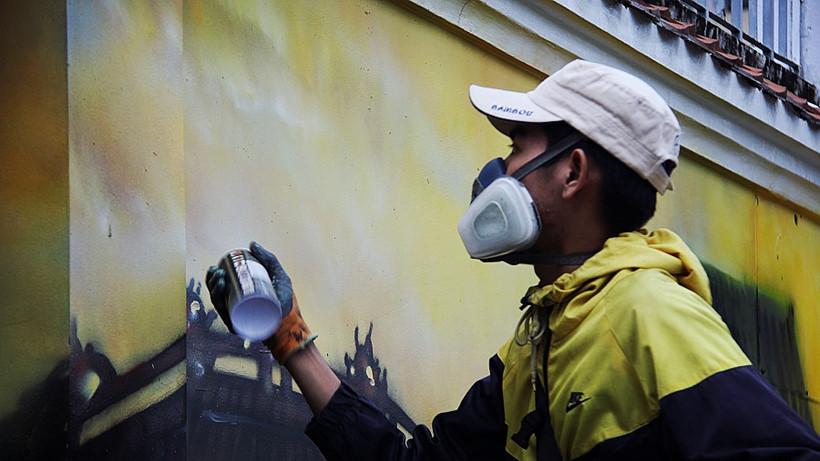 Nguyễn Tấn Lực đang thi công một phần của bức tranh