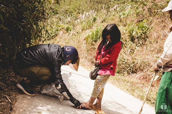 Một bé gái bẽn lẽn khi được anh chàng phượt thủ ướm đôi dép mới - Ảnh: P.H