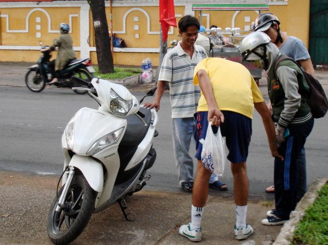 Một bạn gái té xe trên đường Nam Kỳ Khởi Nghĩa (Q.1, TP.HCM) được nhiều người xung quanh vội vã đỡ xe, kiểm tra thương tích cẩn thận  - Ảnh: M.C