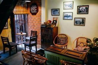 """Men theo con hẻm nhỏ trên đường Bùi Viện, khách đến quán cà phê dễ dàng nhận ra dòng chữ: """"Hà Nội không vội được đâu"""" trên bức tường màu vàng. Tuy không gian quán hẹp, nhưng hầu hết khách đến đây đều tấm tắc khen cách bài trí và thức uống ở đây. Nhiều du khách nước ngoài cũng được bạn bè giới thiệu và tìm đến."""