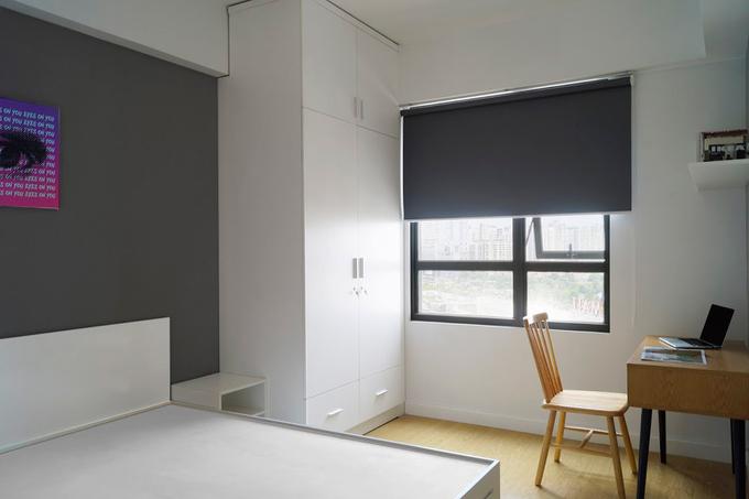 Phòng ngủ với tông màu trung tính có đầy đủ tủ, kệ, bàn làm việc.