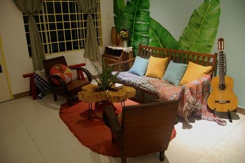 Đầu tiên là khu vực phòng khách toát lên vẻ mộc mạc nhờ bộ bàn ghế kiểu cũ, những chiếc thảm, gối trang trí cũng được khoác lên họa tiết, màu sắc thường dùng trong những năm 90. Hoàn thiện cho vẻ đẹp đơn sơ đó là tấm rèm cửa họa tiết hoa nhí, được treo lên một cách ngẫu hứng.