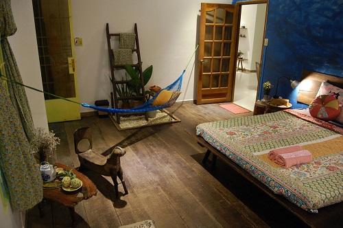 Kế tiếp là không gian phòng ngủ chính, vừa rộng rãi vừa thoáng mát. Điểm nhấn của căn phòng là chiếc giường theo kiểu sập cổ xưa cùng bộ chăn, ga trải giường thường dùng trong những ngày thời bao cấp. Bên cạnh còn điểm xuyết chiếc võng nhỏ độc đáo.