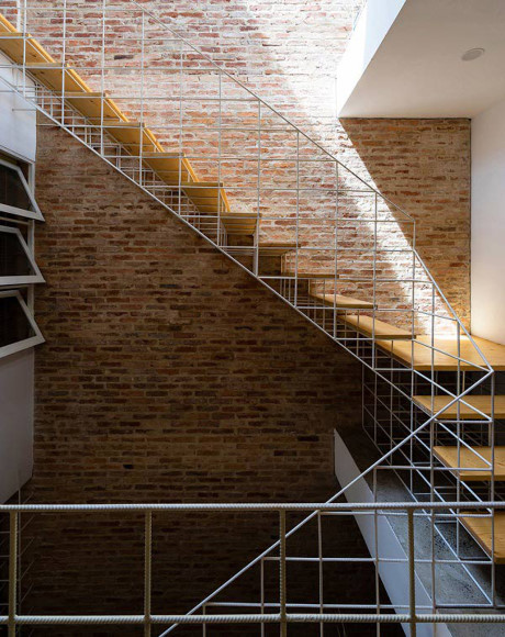 Thiết kế cầu thang với khung thép trắng và bậc gỗ ngay dưới khu vực giếng trời khiến cho căn nhà luôn ngập tràn ánh sáng và không bị ngột ngạt hay bí bích.