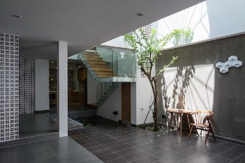"""Ngôn ngữ """"gạch xếp"""" lại được sử dụng môt lần nữa trong nột thất. Tường gạch ống nửa kín nửa hở kết hợp với cây xanh giúp ngôi nhà thêm trong trẻo."""