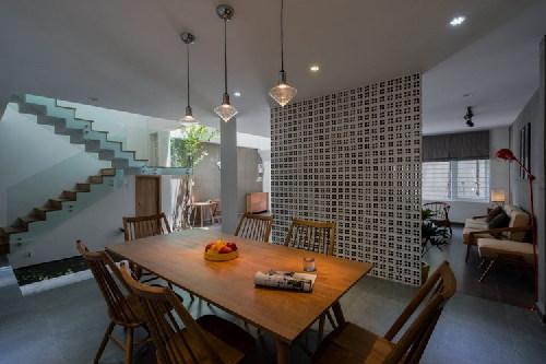 Phòng ăn ngăn cách với khu vực tiếp khách bằng tường gạch lỗ.
