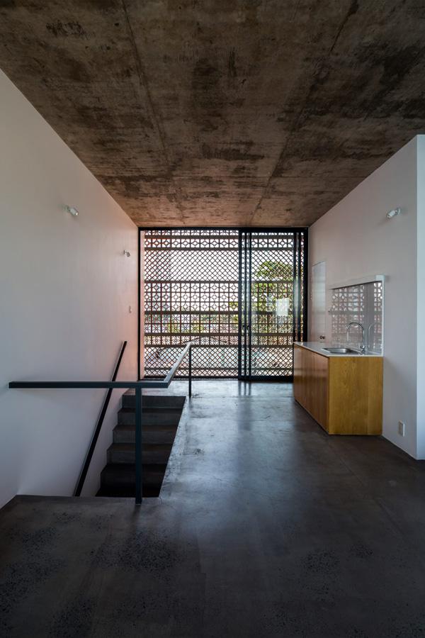 Trần bê tông và bức tường sơn trắng làm nền cho nội thất gỗ bàn bếp, giường, tủ.